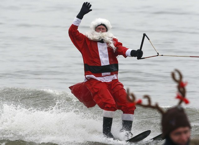 A water skier, dressed as Santa, and another, dressed as a Reindeer, take part in the 29th annual Christmas Eve water performance on the Potomac River in Alexandria, Virginia, December 24, 2014. (Photo by Larry Downing/Reuters)