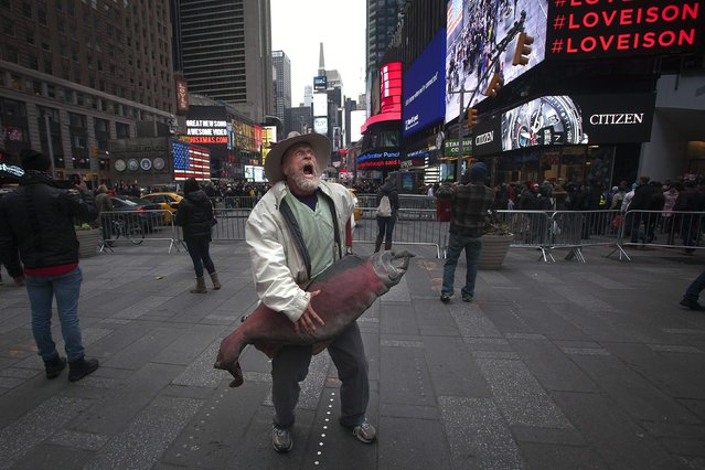 A man sings and dances with a giant fish in Times Square in the Manhattan borough of New York, December 20, 2014. (Photo by Carlo Allegri/Reuters)