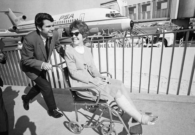 Nancy Reagan, in a knee-length cast, is pushed to waiting plane for return trip to Sacramento, April 3, 1970. The governor's wife broke a bone in her right foot while racing with her 12-year-old son, Skipper, in her Sacramento backyard April 2. Despite the pain and cast, she flew to Los Angeles April 3 to keep an appointment. (Photo by George Brich/AP Photo)