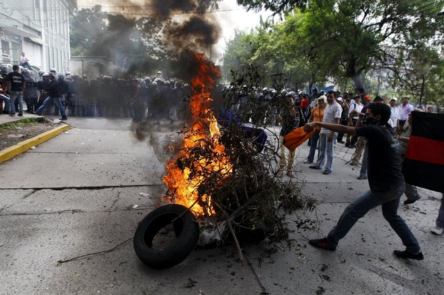 Supporters of David Romero, journalist and director of opposition broadcaster Globo, burn branches during a protest outside the Supreme Court in Tegucigalpa, Honduras, November 13, 2015. Romero, a journalist strongly critical of the Honduras Government was sentenced on Friday on charges of defamation and libel after reporting a case of public corruption that  splashed President Orlando Hernandez last year. (Photo by Jorge Cabrera/Reuters)