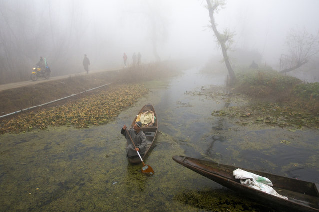 A Kashmiri boatman rows his boat in the interiors of the Dal Lake surrounded by dense fog on a cold morning in Srinagar, Indian controlled Kashmir, Indian controlled Kashmir, Thursday, December 3, 2020. (Photo by Dar Yasin/AP Photo)