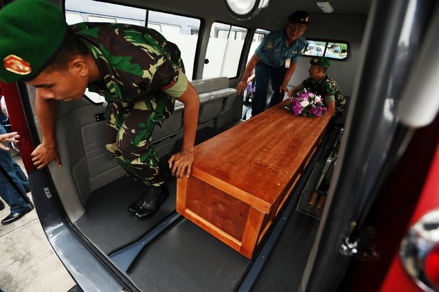 Indonesian soldiers place a coffin containing a victim of the AirAsia flight QZ8501 crash into a vehicle at Indonesian Military Base Airport on December 31, 2014 in Surabaya, Indonesia. (Photo by Robertus Pudyanto/Getty Images)