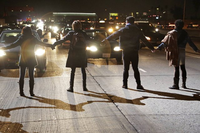 Protesters block the southbound lanes of the 110 freeway after the Los Angeles County Coroner released an autopsy report on the LAPD's shooting of Ezell Ford in Los Angeles, California December 29, 2014.  Ford, an unarmed 25-year-old black man slain by Los Angeles police officers in August suffered three gunshot wounds, including one to his back, a long-awaited autopsy report into the killing showed on Monday. (Photo by Jonathan Alcorn/Reuters)