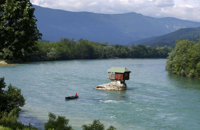 A man rows a boat near a house built on a rock on the river Drina near the western Serbian town of Bajina Basta, about 160km (99 miles) from the capital Belgrade May 22, 2013. The house was built in 1968 by a group of young men who decided that the rock on the river was an ideal place for a tiny shelter, according to the house's co-owner, who was among those involved in its construction. (Photo by Marko Djurica/Reuters)