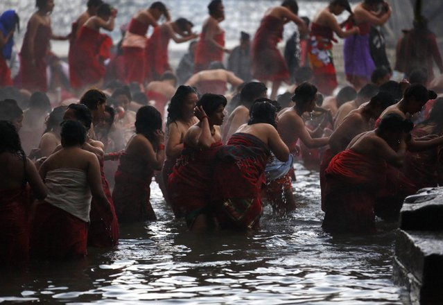 Devotees return after taking a holy bath at the Saali River on the first day of the Swasthani Brata Katha festival at Sankhu in Kathmandu January 5, 2015. (Photo by Navesh Chitrakar/Reuters)