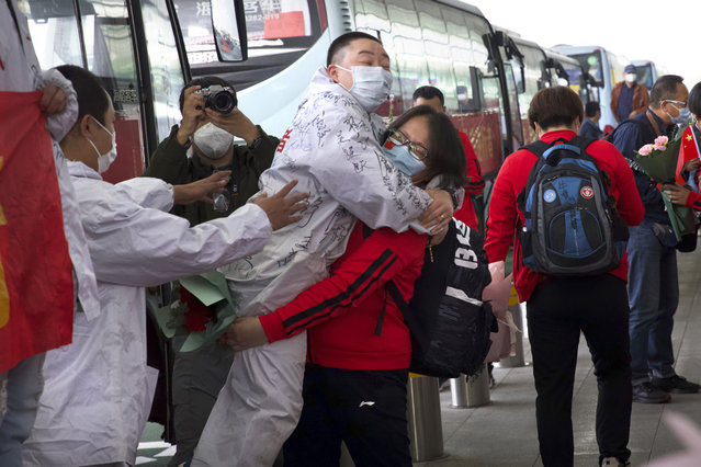 A medical worker from China's Jilin Province, in red, embraces a colleague from Wuhan as she prepares to return home at Wuhan Tianhe International Airport in Wuhan in central China's Hubei Province, Wednesday, April 8, 2020. Within hours of China lifting an 11-week lockdown on the central city of Wuhan early Wednesday, tens of thousands people had left the city by train and plane alone, according to local media reports. (Photo by Ng Han Guan/AP Photo)