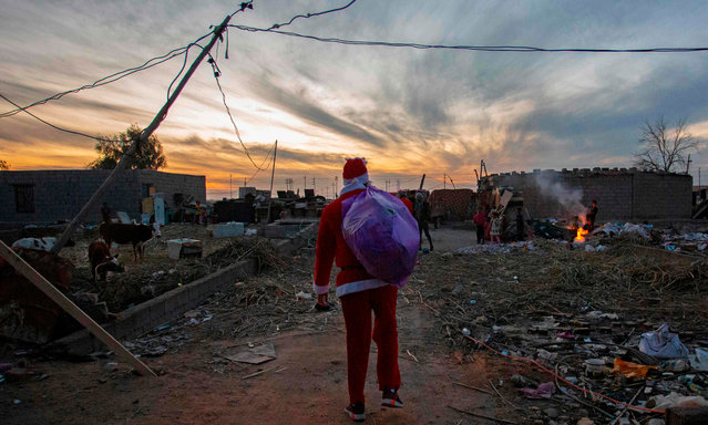 A man dressed as Santa Claus arrives to distribute toys on children living in an impoverished neighbourhood in Iraq's southern city of Basra on December 26, 2020. (Photo by Hussein Faleh/AFP Photo)