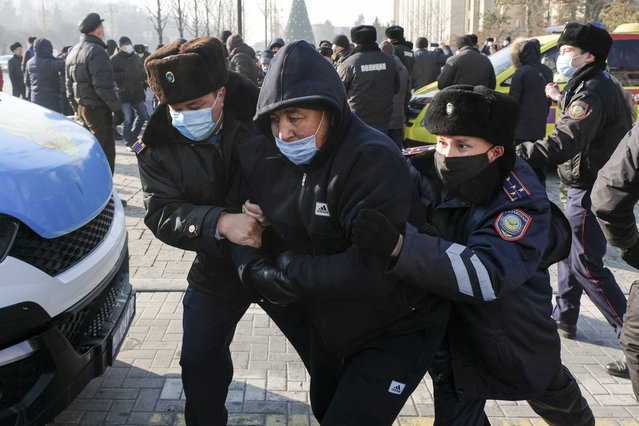 Kazakhstan's police officers detain a protester during an opposition rally in Almaty, Kazakhstan, Sunday, January 10, 2021, as voters in resource-rich Kazakhstan are going to the polls in a parliamentary election lacking any serious opposition. Dozens of activists were detained in at least three major cities, including the capital, Nur-Sultan, and Almaty, with reports of independent observers being denied access or detained at some polling stations. (Photo by Vladimir Tretyakov/AP Photo)