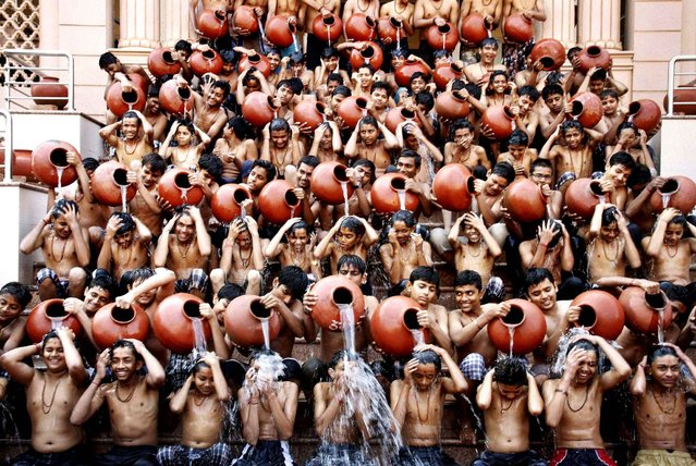 Indian students pour water on each other as part of a ritual bath on the eve of Magh Purnima in Ahmadabad, India, Sunday, January 4, 2015. Many Hindu devotees take holy bath during the auspicious festival hoping that their sins are washed away according to ancient Hindu tradition. (Photo by AP Photo/Press Trust of India)