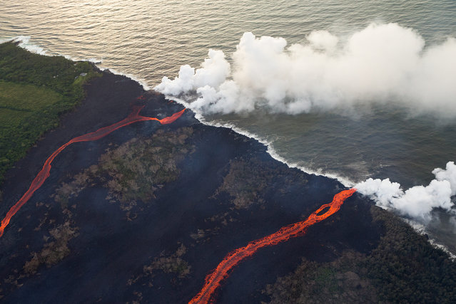 Two rivers of lava enter the sea on May 24, 2018 in Hawaii, USA, as multiple fissure eruptions supplied a tremendous volume of molten material, and the interaction between the cold seawater and 2000 degree lava create a toxic gas plume of laze. Consisting of hydrochloric acid, steam, and tiny bits of volcanic glass, this mixture irritates and burns, and can cause respiratory issues. (Photo by Bruce Omori/Paradise Helicopters/ZUMA Wire/Rex Features/Shutterstock)