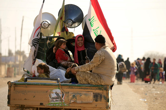 Displaced people who had fled from Hammam al-Alil, south of Mosul, ride a military vehicle to head to safer territory, Iraq November 6, 2016. (Photo by Thaier Al-Sudaini/Reuters)