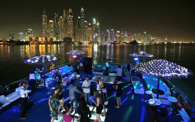 In this April 22, 2015 photo, guests dance on the GuGu boat during a private party opposite the skyline of the Marina Waterfront in Dubai, United Arab Emirates. Dubai's year-round sunshine gives Marina a summer-vibe throughout the winter months, when temperatures rarely drop below a comfortable 75 degrees Fahrenheit (24 Celsius) during the day. On weekends, alcohol-fueled party boats ferry Russian and Western expatriates down the canal as speed boats and jet skis come out for a ride. (Photo by Kamran Jebreili/AP Photo)
