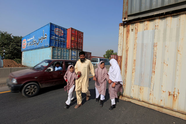 A man with his children walk past containers, which will be used to block roads during a planned protest called by political party Pakistan Tehreek-e-Insaf (PTI) in Islamabad, Pakistan, October 31, 2016. (Photo by Faisal Mahmood/Reuters)