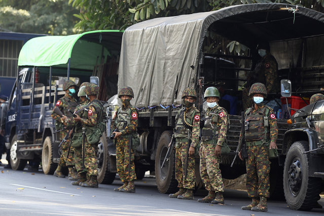 Soldiers stand next to a military truck parked near the headquarters of the National League for Democracy party in Yangon, Myanmar Monday, February 15, 2021. (Photo by AP Photo/Stringer)