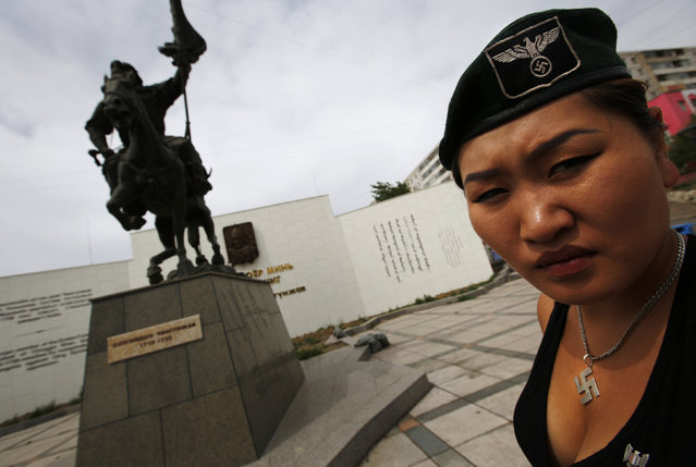 Uranjargal, a leader of the Mongolian neo-Nazi group Tsagaan Khass, stands next to a statue of Chingunjav, a Mongolian national hero, in Ulan Bator June 22, 2013. (Photo by Carlos Barria/Reuters)
