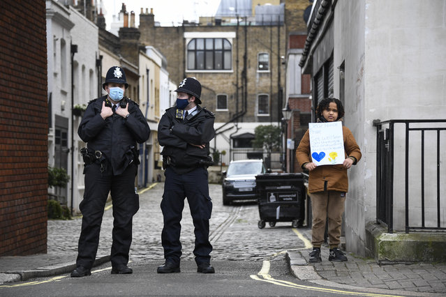 A child poses with a Get Well message for Prince Philip, as police officers patrol the side entrance of the King Edward VII Hospital in London, Saturday, February 20, 2021. Buckingham Palace said the husband of Queen Elizabeth II, 99-year-old Prince Philip was admitted to the private King Edward VII Hospital on Tuesday evening after feeling unwell. (Photo by Alberto Pezzali/AP Photo)