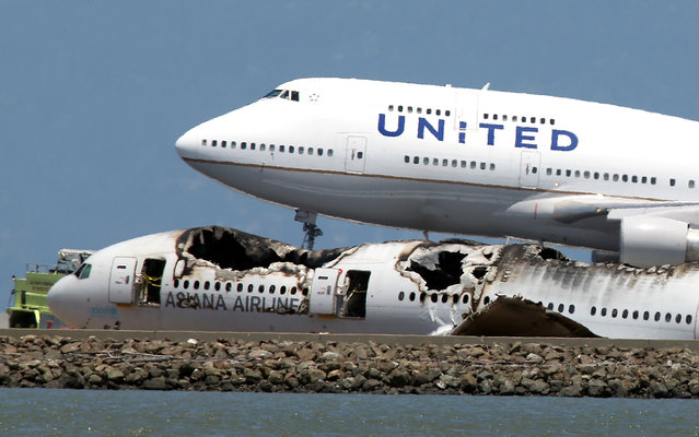 A United Airlines 747 lands next to the wreckage of Asiana Airlines flight 214 as it sits on runway 28L at San Francisco International Airport on July 8, 2013 in San Francisco, California. Two days after Asiana Airlines flight 214 crash landed at San Francisco International Airport, the National Transportation Safety Board (NTSB) is continuing their investigation as to why the plane crashed. (Photo by Justin Sullivan/AFP Photo)