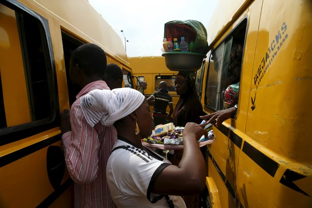 Vendors sell their wares at a parking garage for commercial transports in Obalende district in Nigeria's commercial capital Lagos November 23, 2015. (Photo by Akintunde Akinleye/Reuters)