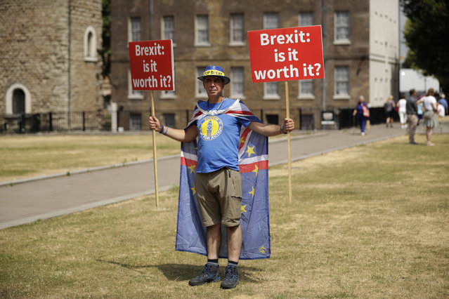 Anti-Brexit, pro-EU supporter Steve Bray holds placards on Abingdon Green across the road from the Houses of Parliament in London, Monday, July 9, 2018. Former U.K. Brexit Secretary David Davis said Monday that he won't seek to challenge Prime Minister Theresa May's leadership after resigning from her Cabinet, but will aim to pressure her to toughen her position on Britain's departure from the European Union. (Photo by Matt Dunham/AP Photo)
