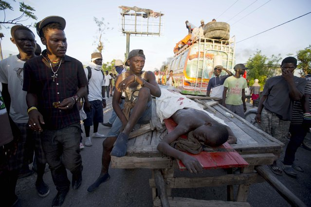 In this November 1, 2016, photo, protesters carry the body of a young teenager on a cart after he was shot amid protests over delays in aid distribution after a Category 4 hurricane pummeled the Caribbean country last month, in Les Cayes, Haiti. Mayor Jean Gabriel Fortune said the boy was killed as police clashed with protesters when they tried to climb aboard a boat that had arrived from Puerto Rico carrying supplies. (Photo by Dieu Nalio Chery/AP Photo)