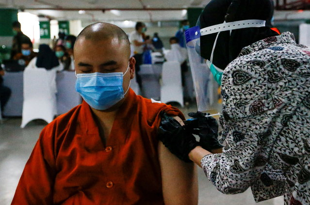 A monk reacts while receiving the first dose of China's Sinovac Biotech vaccine for the coronavirus disease (COVID-19) during the mass vaccination program for clergy at the parking lot of Grand Istiqlal Mosque in Jakarta, Indonesia, February 25, 2021. (Photo by Ajeng Dinar Ulfiana/Reuters)