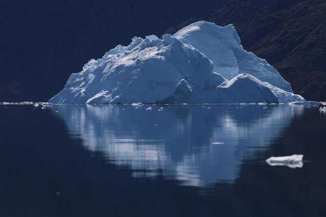 An iceberg floats through the water near Ilulissat, Greenland, on July 21, 2013. (Photo by Joe Raedle/Getty Images via The Atlantic)