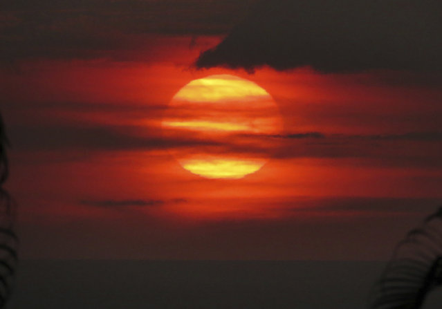 """In this May 23, 2018, photo provided by Chris Stewart the sun sets through """"vog"""", or volcanic smog, in Kailua-Kona, Hawaii. Kilauea volcano on Hawaii's Big Island has had it all over the past three weeks: molten rock shooting toward the sky, lava oozing from the ground and ash clouds rising miles into the air. You can also add """"vog"""" to the mix. Retired photojournalist Chris Stewart says there's one good thing about vog: It intensifies the colors of a sunset. But it depends on how thick the haze is. """"Some days it's thin enough you can see the sun passing through"""", he said. """"But other days we just go inside because we can't see it at all"""". (Photo by Chris Stewart via AP Photo)"""