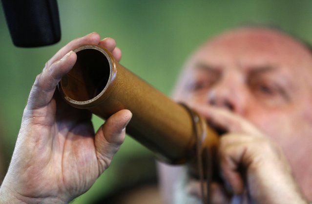 "A competitor uses a specially designed instrument at the German championships in Deer-Calling at the ""Jagd & Hund"" exhibition in Dortmund February 6, 2015. (Photo by Ina Fassbender/Reuters)"