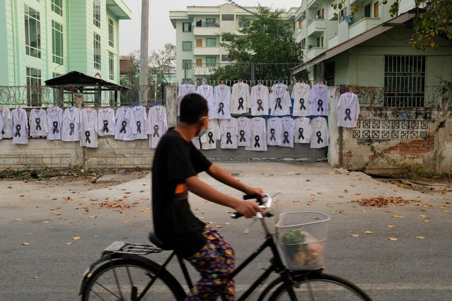 This photo taken and received from an anonymous source via Facebook on March 26, 2021 shows a man looking at white uniforms with black ribbons hanging on the fence of th University of Medicine, Mandalay as part of protest by members of medical community in Mandalay against the military coup. (Photo by Handout/Facebook via AFP Photo)