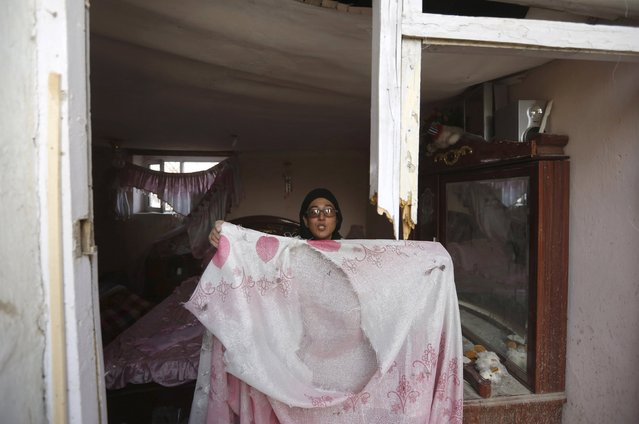 """An Afghan woman shows a bed cover after a suicide attack on French restaurant  """"Le Jardin"""" in Kabul, Afghanistan January 2, 2016. (Photo by Mohammad Ismail/Reuters)"""