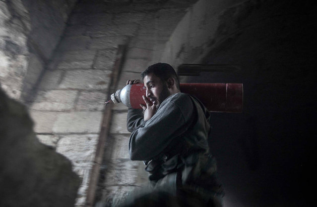 A rebel fighter carries an improvised explosive device as they try to repel a coordinated attack using mortar, tank and aerial artillery fire carried out by loyalists to President Bashar Assad in the Jedida district of Aleppo, on November 3, 2012. (Photo by Narciso Contreras/AP Photo)