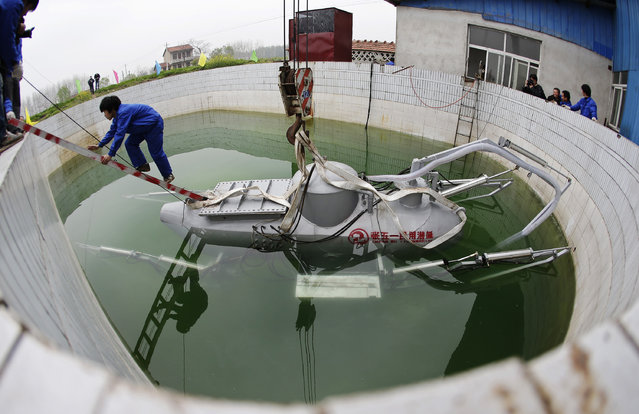 A worker climbs up from Zhang Wuyi's newly designed unmanned submarine that captures sea cucumbers, during a test operation at an artificial pool near a shipyard in Wuhan, Hubei province, March 26, 2013. Zhang, a 38-year-old local farmer who is interested in scientific inventions, has independently made eight miniature submarines with several fellow engineers, one of which was sold to a businessman in Dalian at a price of 100,000 yuan ($15,855) in 2011. The submarines, mainly designed for harvesting aquatic products, such as sea cucumber, have a diving depth of 20-30 metres (66-98 feet), and can travel for 10 hours, local media reported. (Photo by Reuters/Stringer)