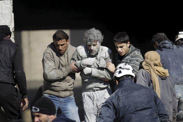 Residents help an injured man in a site hit by what activists said were airstrikes carried out by the Russian air force in the rebel-controlled area of Maaret al-Numan town in Idlib province, Syria January 9, 2016. (Photo by Khalil Ashawi/Reuters)
