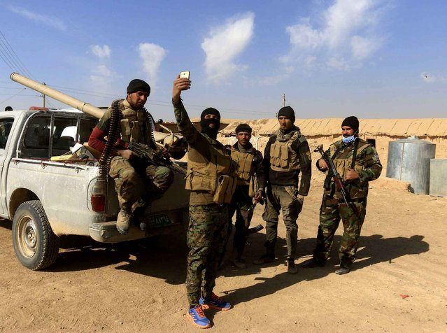 "Fighters of Popular Mobilization Forces take a photo at the fighting lines against Islamic State Group militants outside Mosul, Iraq, Saturday, November 26, 2016. Iraq's parliament on Saturday voted to accord full legal status to government-sanctioned Shiite militias as a ""back-up and reserve"" force for the military and police and empower them to ""deter"" security and terror threats facing the country, like the Islamic State group. (Photo by Anmar Khalil/AP Photo)"