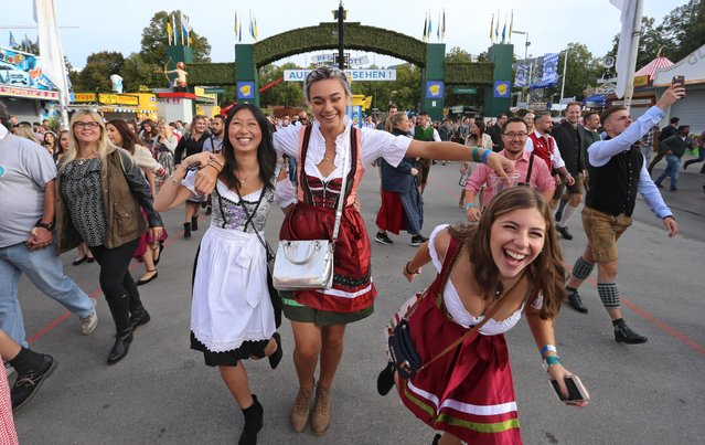 Women wearing Dirndl, a traditional Alpine folk dress, run to get a place in a tent for the opening of the 185th Oktoberfest beer festival in Munich, Germany, 22 September 2018. (Photo by Karl- Josef Hildenbrand/DPA/Alamy Live News)