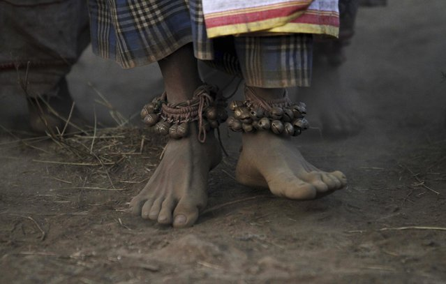 A member of India's Dongria tribe wearing traditional anklets dances near their deity's worship venue during the two-day long Niyamraja Festival atop the Niyamgiri hills near Lanjigarh in Kalahandi district, Orissa state, India, Sunday, February 22, 2015. (Photo by Biswaranjan Rout/AP Photo)
