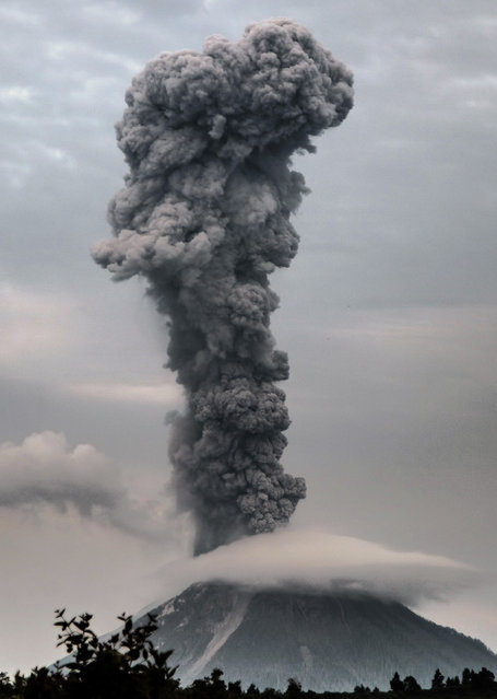 Mount Sinabung volcano spews thick volcanic ash, as seen from the town of Brastagi in Karo, North Sumatra province, on May 30, 2017. Sinabung roared back to life in 2010 for the first time in 400 years and after another period of inactivity, erupted once more in 2013 and has remained highly active since. (Photo by Tibta Pangin/AFP Photo)