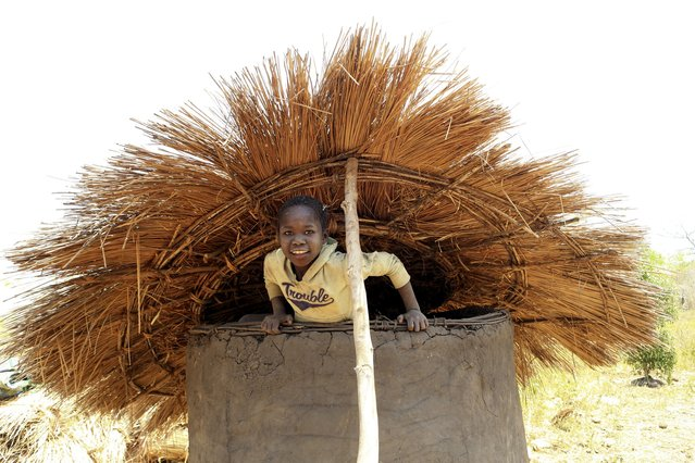 A girl attempts to climb out of a granary after cleaning it in preparation for grain storage in Odek village, north of Uganda capital Kampala February 14, 2015. (Photo by James Akena/Reuters)