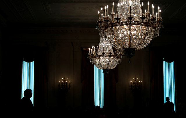 President Trump is silhouetted in a window of the East Room as he participates in a ceremony awarding a Medal of Honor posthumously to Air Force Technical Sergeant John A. Chapman at the White House on August 22, 2018. (Photo by Leah Millis/Reuters)