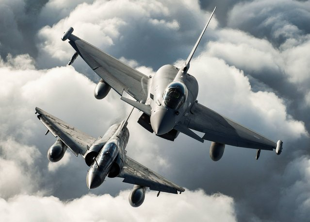 Ministrey of Defence undated handout photo of a RAF Typhoon of 1(F) Sqn and a French Air Force Mirage 2000N (bottom) practice their formation flying skills as part of Ex Capable Eagle over the skies of RAF Leeming in North Yorkshire, on October 15, 2013.  (Photo by Sgt Ralph Merry ABIPP RAF/PA Wire)