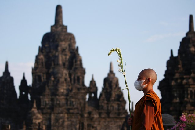 A Buddhist monk wearing a protective mask walks around the Sewu temple during the celebrations of Vesak Day, marking the birth, enlightenment and death of Buddha, amid the coronavirus disease (COVID-19) pandemic in Sleman, Yogyakarta, Indonesia, May 26, 2021. (Photo by Willy Kurniawan/Reuters)