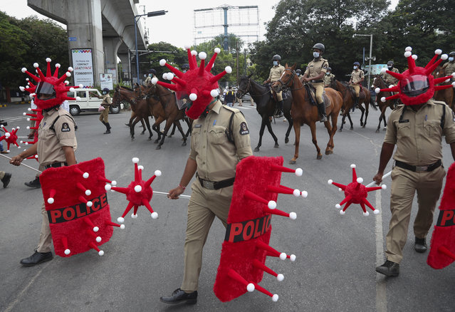 Indian police officers walk wearing virus themed helmet during an awareness drive aimed at preventing the spread of the coronavirus in Hyderabad, India, Wednesday, June 9, 2021. (Photo by Mahesh Kumar A./AP Photo)