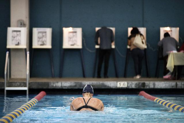 Sarah Salem, 34, swims as voters cast their ballots at Echo Deep Pool Tuesday, November 6, 2018, in Los Angeles. (Photo by Jae C. Hong/AP Photo)