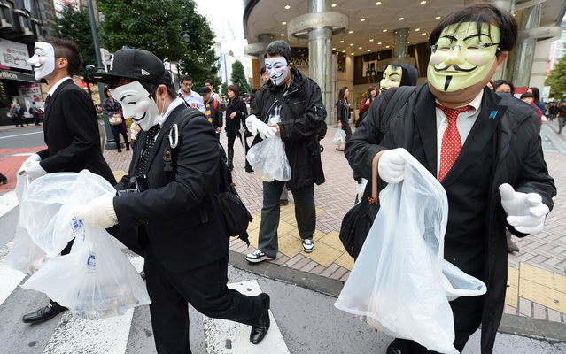 People wearing masks walk with plastic bags to pick up litter on the street in Tokyo on November 4, 2013. A dozen people took part in the clean up mission organised by hacker collective Anonymous. (Photo by Toru Yamanaka/AFP Photo)