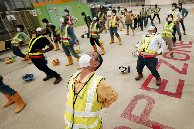 Construction workers perform morning exercises at the start of their shift in Singapore in this June 20, 2013 file photo. Singapore is expected to report PMI numbers for January this week. (Photo by Tim Wimborne/Reuters)