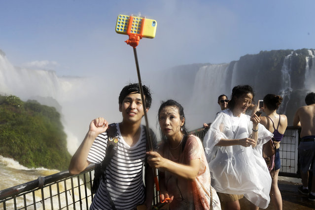 In this Saturday, March 14, 2015 photo, Japanese tourists Hiromi Kanetake, right, and her son Takayuki, photograph themselves with a phone camera as they stand in the spray on the Brazilian side of Iguazu falls, behind, in Foz do Iguazu, Brazil. Iguazu Falls is located on Brazil's border with Argentina. (Photo by Jorge Saenz/AP Photo)