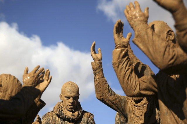 Iranian Shiites cover themselves with mud during Ashoura, marking the death anniversary of Imam Hussein, the grandson of Islam's Prophet Muhammad, at the city of Bijar, west of the capital Tehran, Iran, Thursday, November 14, 2013. (Photo by Ebrahim Noroozi/AP Photo)