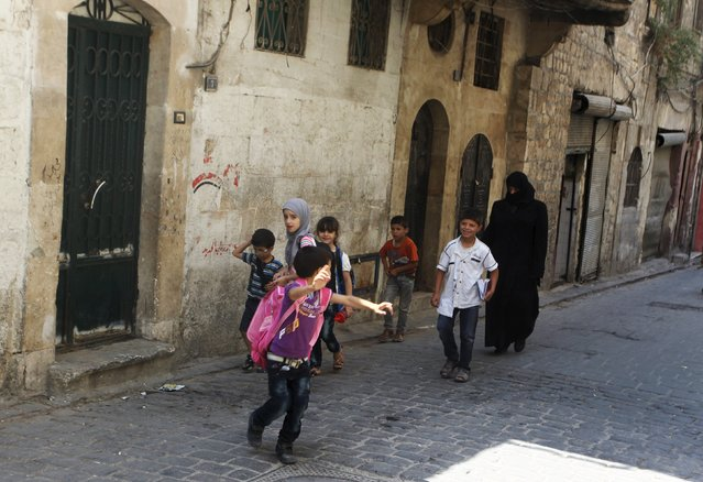 A woman walks with schoolchildren along a street in the old city of Aleppo, Syria August 24, 2015. (Photo by Abdalrhman Ismail/Reuters)