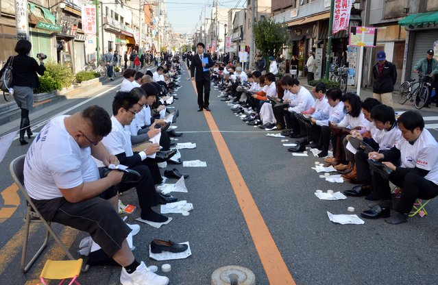 """Some 800 participants polish their leather shoes on a street in Tokyo's Taito ward, a district famous for its shoemakers in Japan, to challenge the record of """"most people polishing shoes"""" for the Guinness Book of World Records on November 22, 2013. Participants established a new world record over the previous one, made with 451 people in the UAE in 2011. (Photo by Yoshikazu Tsuno/AFP Photo)"""