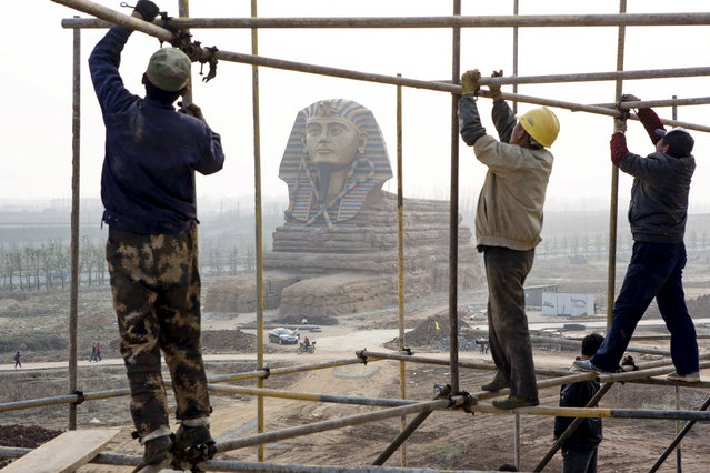 Laborers work on scaffolding near a full-scale replica of the Sphinx at an unfinished movie and animation tourism theme park, in Chuzhou, Anhui province, China, March 27, 2015. A full-scale replica of the Egyptian Great Sphinx is being built at a Chinese amusement park. (Photo by Reuters/China Daily)
